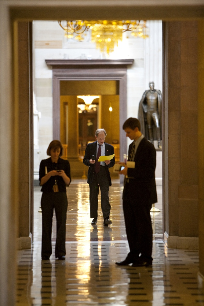 Illinois Representaive Tom Johnson paces the main hall of the U.S. Capital building while working the phones.
