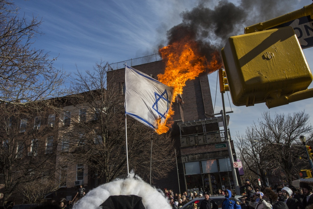 Photography image - Members of the Anti-Zionist group called Neturei Karta (Jewish Babylonian Aramaic: נָטוֹרֵי קַרְתָּא) burn the Israeli flag. Neturei Karta opposes Zionism and calls for a dismantling of the State of Israel, in the belief that Jews are forbidden to have their own state until the coming of the Jewish Messiah. Williamsburg, Brooklyn. March 11, 2017. (Kevin C Downs/ Agence Cosmos)