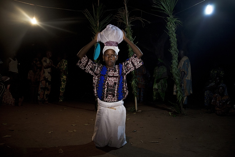 Before Efe, the star mask of Guelede tradition, arrives, a young virgin comes into the arena, holding a closed calabash on her head. She is called 'Arugba'. In the calabash, lays all the mystical power and knowledge of the Mothers, 'Awon Iya' . Ofia, Benin, 2017. ©Laeïla Adjovi