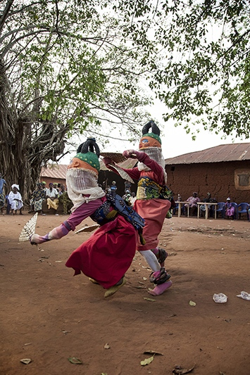 "Jean Idohou, 14, and Germain Abiodoun, 12, have learnt Guelede dances years ago. In this dance called ""Agbaluka"", female masks, with costumes that have fake behinds, come first. Ofia, Benin, 2017. ©Laeïla Adjovi"