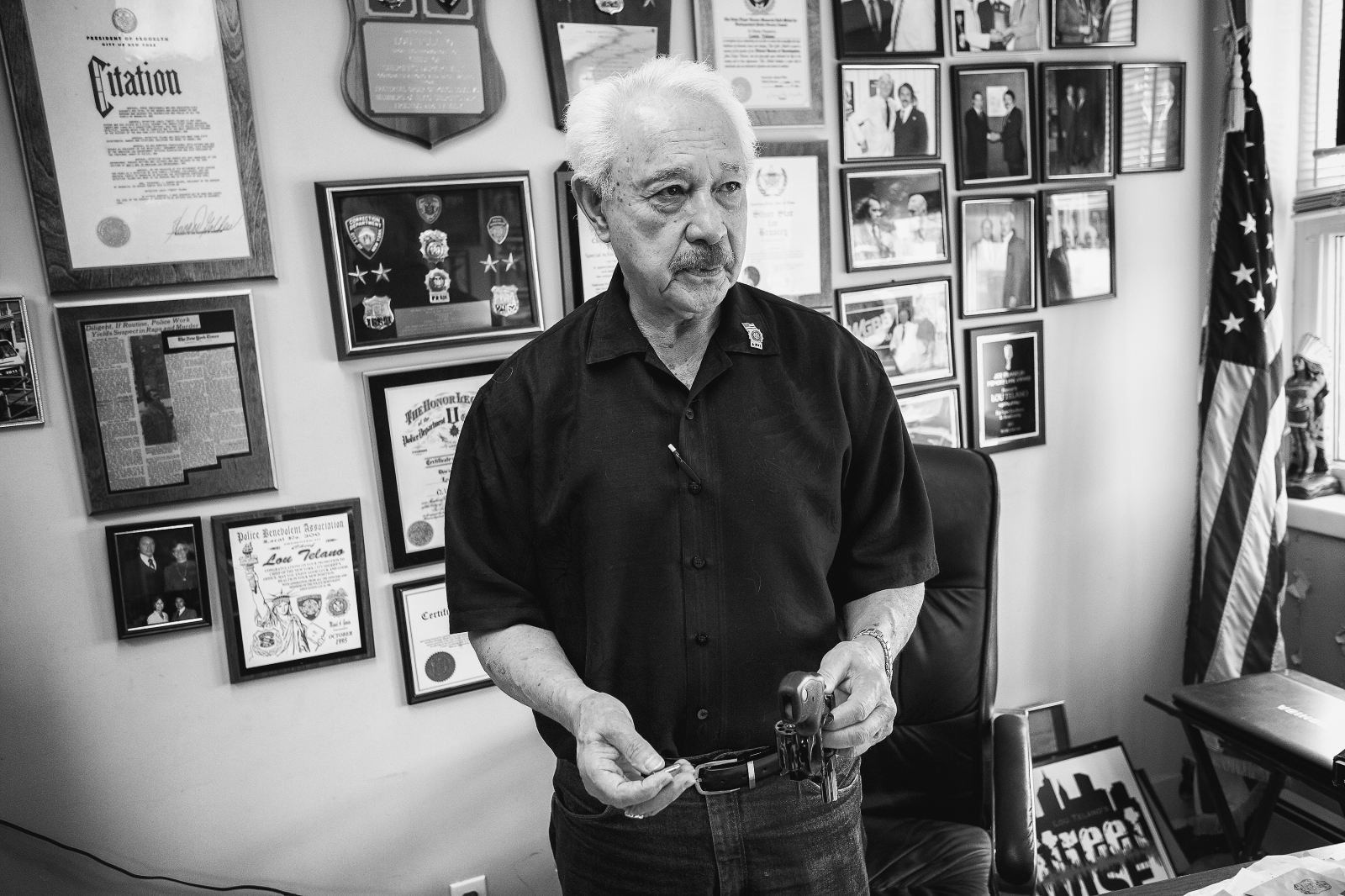 Photography image - Retired Detective Lou Telano (Tanto) loading his 28 Magnum revolver, that holds 8 rounds instead of the usual 6, he explains and he carries it in his pocket. Behind him are his memorabilia from his days in the NYPD. Tanto was his nickname because he looks Native American. (Kevin C. Downs/Agence Cosmos)