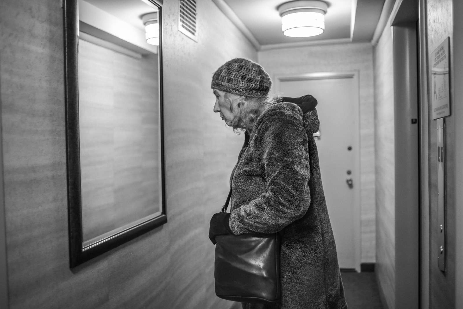 Jennifer checks herself in the hallway mirror of her apartment building before going out to run errands in New York City, Jan. 2, 2017. After ten years of transitioning, Jennifer, together with her partner, Michelle, has finally decided to undergo sex reassignment surgery. The procedure will take place in Philadelphia on January 11th.