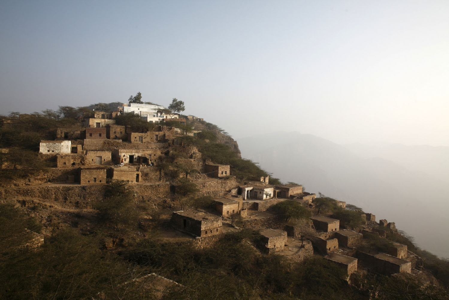 Perched on a mountain top, this small village is occupied entirely by salt miners who work in the Khewra salt mine below them. Punjab, Pakistan.