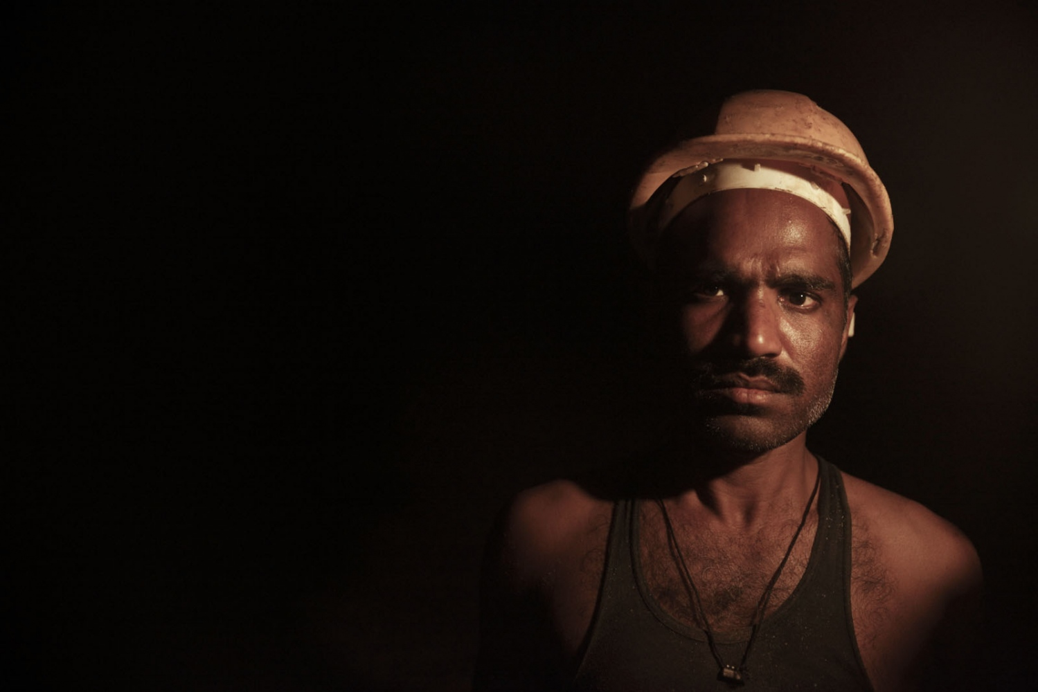 A salt workers in the darkness of the Warcha salt mine. Punjab, Pakistan.