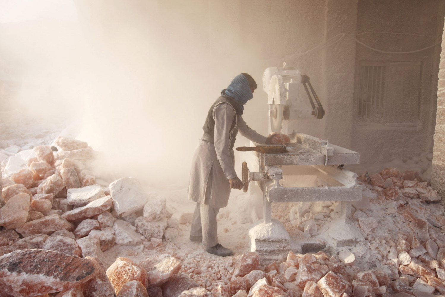A salt cutting workshop uses a mechanised saw to cut up the salt in to blocks sending salt dust in to the air. Local people also carve the beautiful pink rock salt in household objects ranging from ashtrays to lamps which are then send and sold at tourist shops. Punjab, Pakistan.