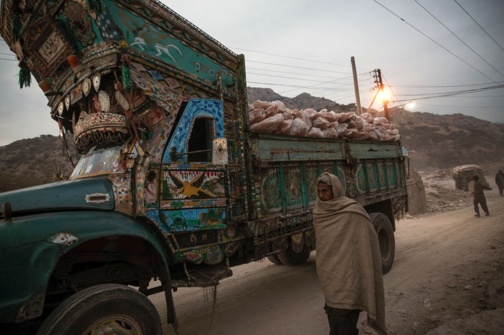 A truck laden with tonnes of rock salt leaves the Warcha salt mine at dusk. Punjab, Pakistan.