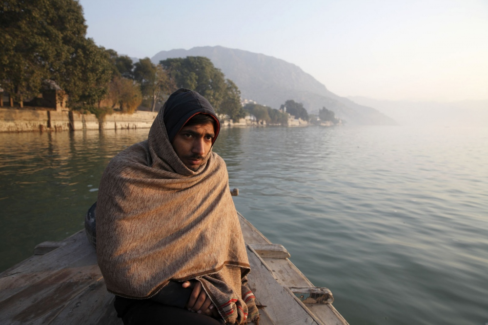 A Pakistani man sits on a boat that ferries people to the kalabargh salt mine.  Punjab, Pakistan.