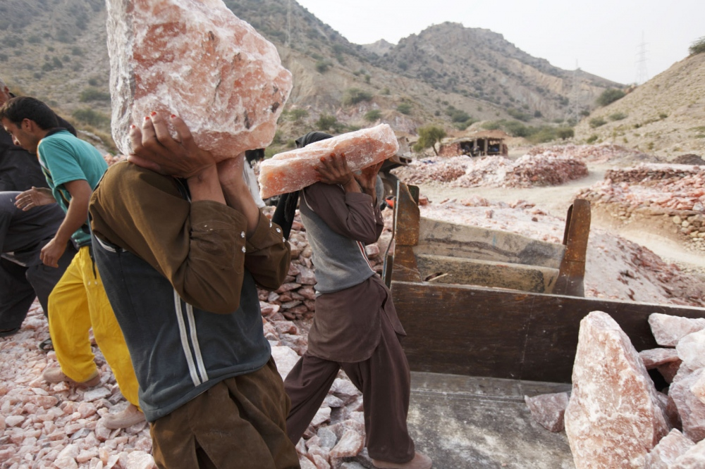 Men loads up a trailer with large pieces of pink rock salt recently excavated from the Kalabargh salt mine.  Punjab, Pakistan.
