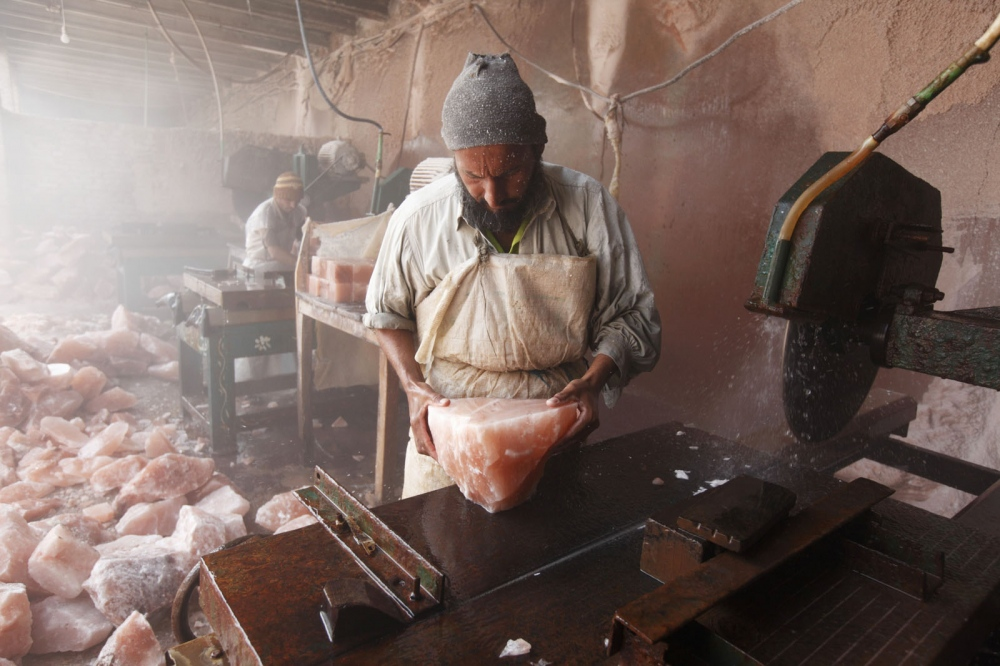 In a salt cutting factory near Kalabargh, a man from Karachi works cutting salt blocks in to smaller cubes with a circular saw. These salt blocks are then carve further to make objects for the tourist souvenir market such as candle holders and ashtrays. Punjab, Pakistan.