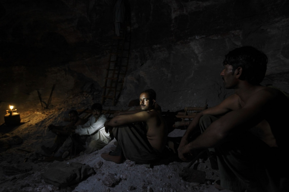 A group of salt miners take a rest inside the dark depths of the Khewra salt mine. Punjab, Pakistan.