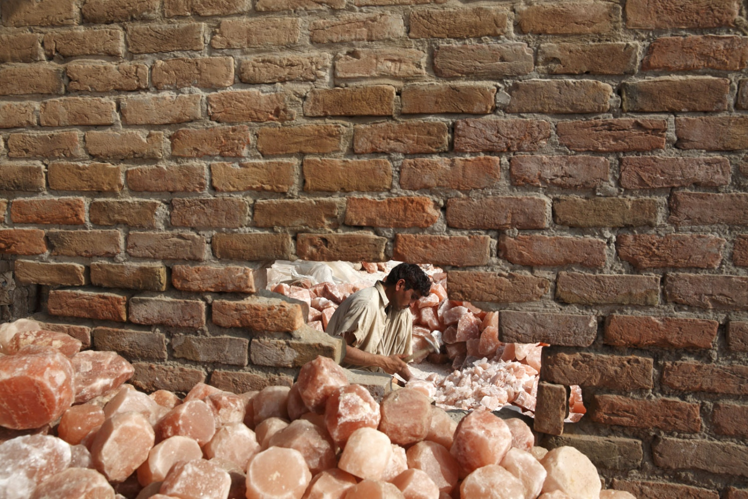 At a salt carving factory a many trims salt bricks in to cubes ready to be carved in to objects such as candle holders or ash-trays. Punjab, Pakistan.