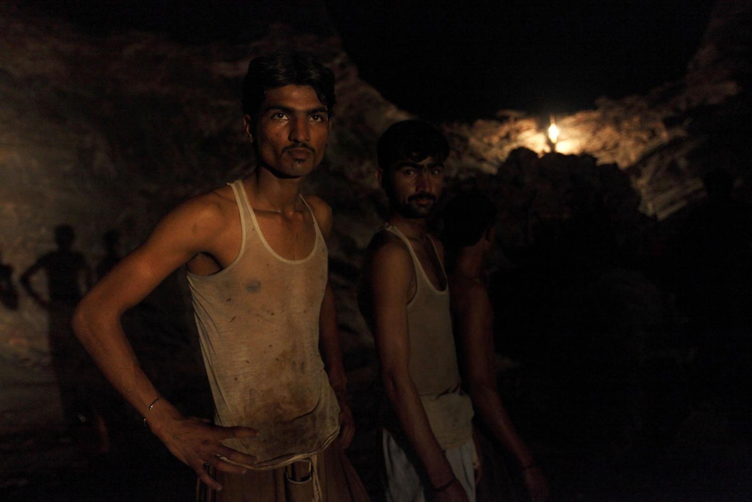 Miners pause in teh darkness of the Khewra Salt Mine. Punjab, Pakistan.