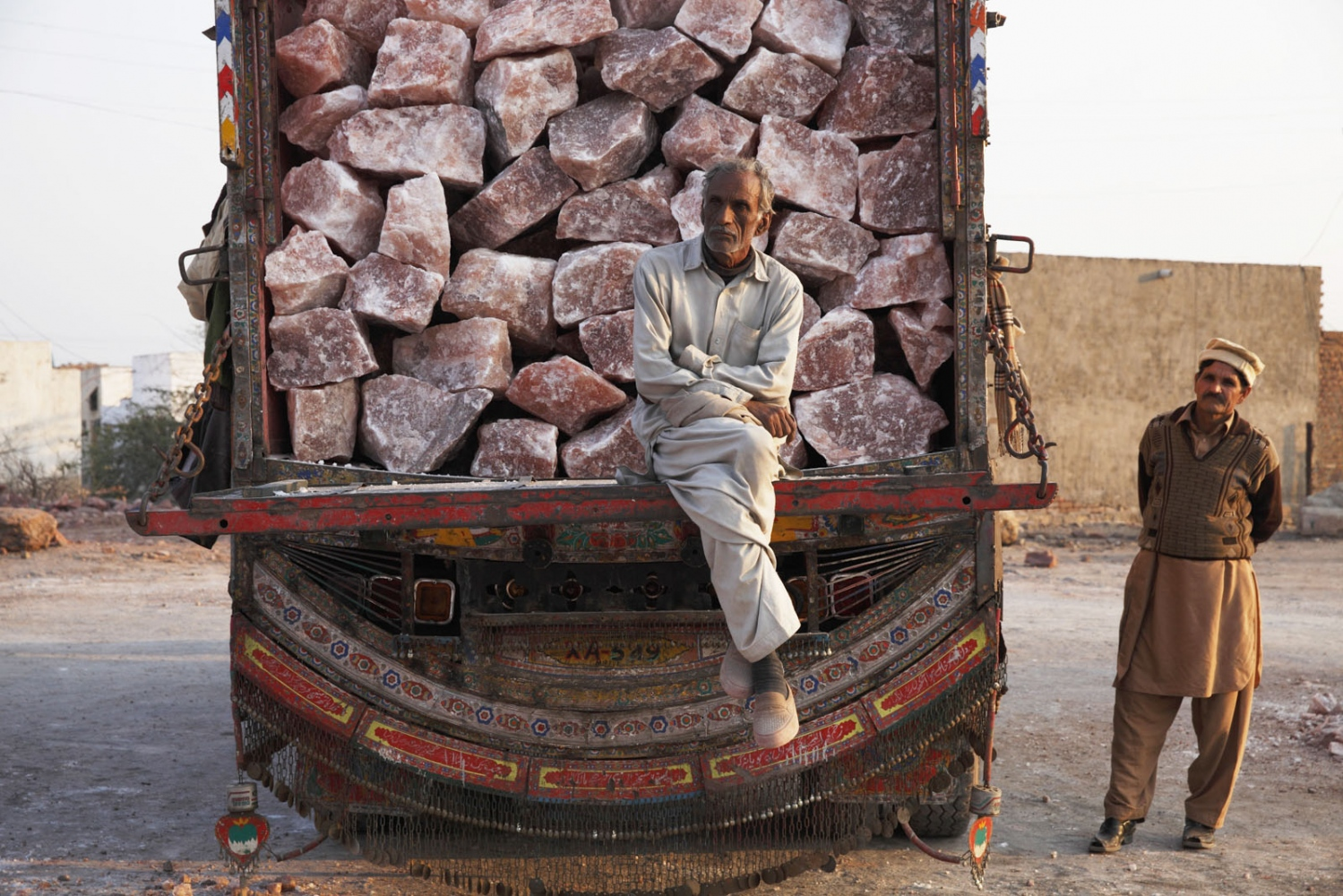 Men load a truck with salt from Khewra Salt mine to be driven south to Karachi. Very few places in the world have pink rock salt and Pakistan holds by far the most. Punjab, Pakistan.