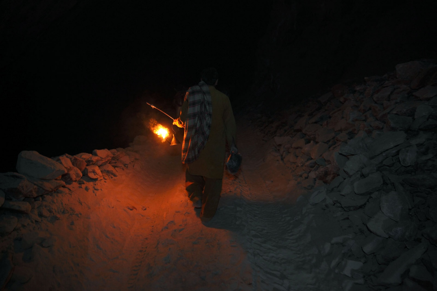 A salt miner walks through the mine after his shift has finished at the Kalabagh salt mine. Light from his small oil-burning lantern is all he has to find his way out. Punjab, Pakistan.