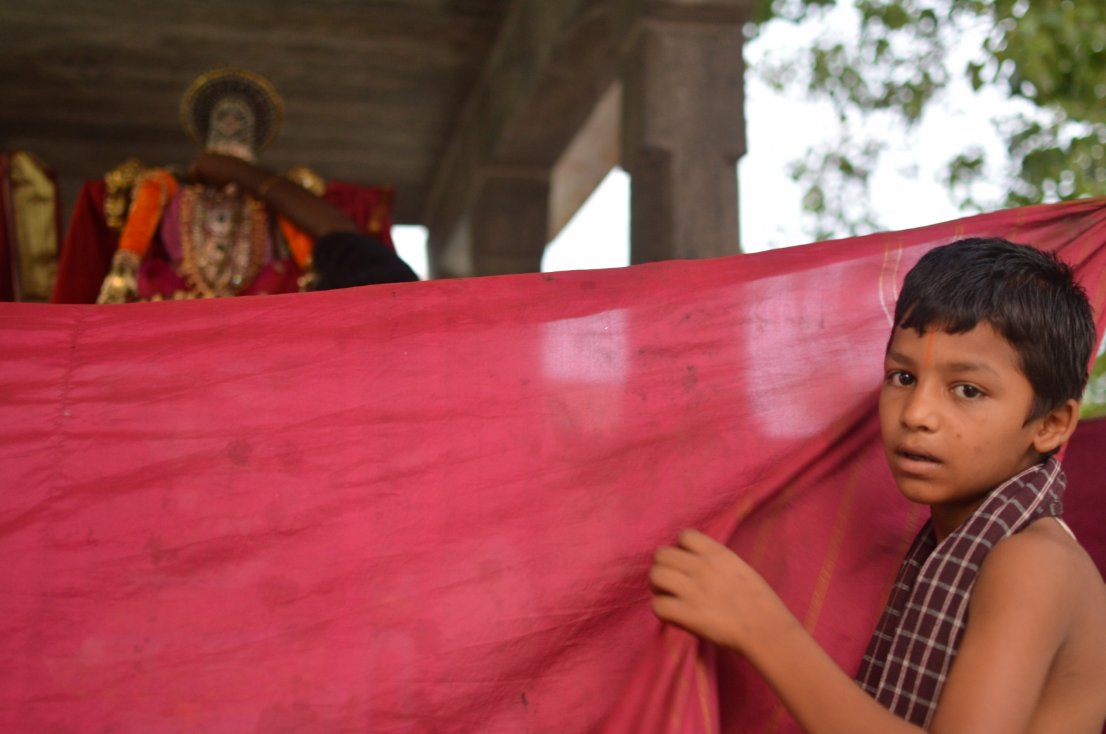 A young boy hides the preparation of a religious festival taking place in late May in Kanchipuram, India.