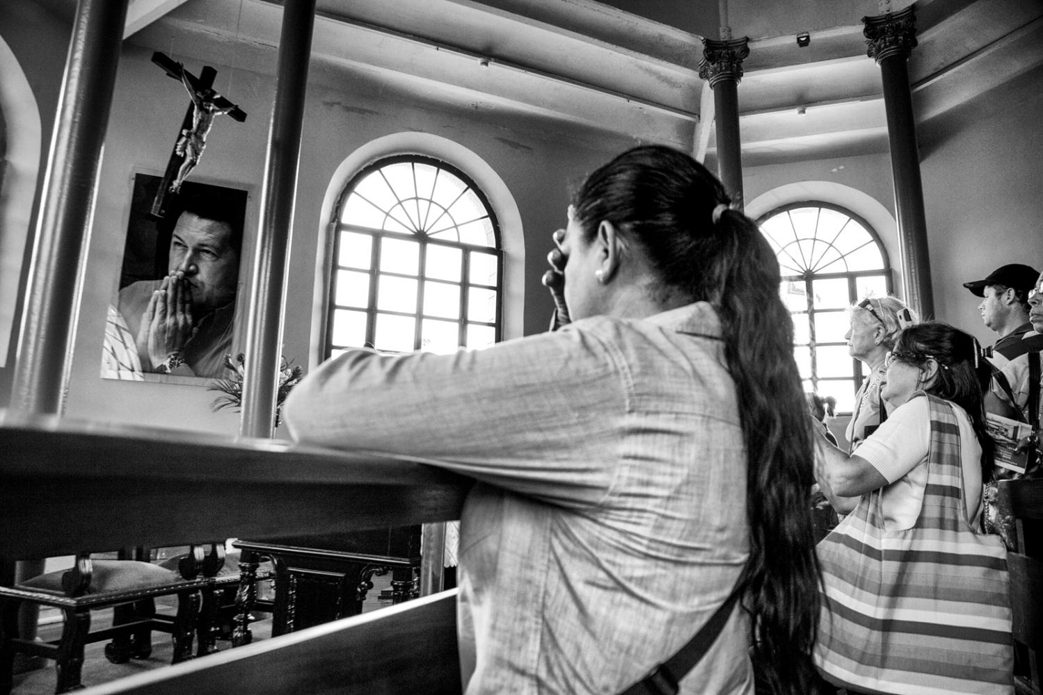 In the Chapel of the Cuartel de la Montaña the visitors pray in front of Chávez's photo.