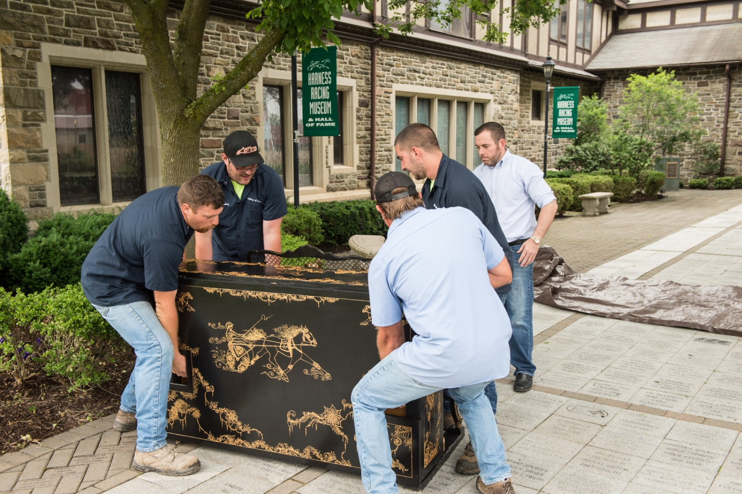 Placing a finished piano in its final location outside the Harness Racing Museum in Goshen.