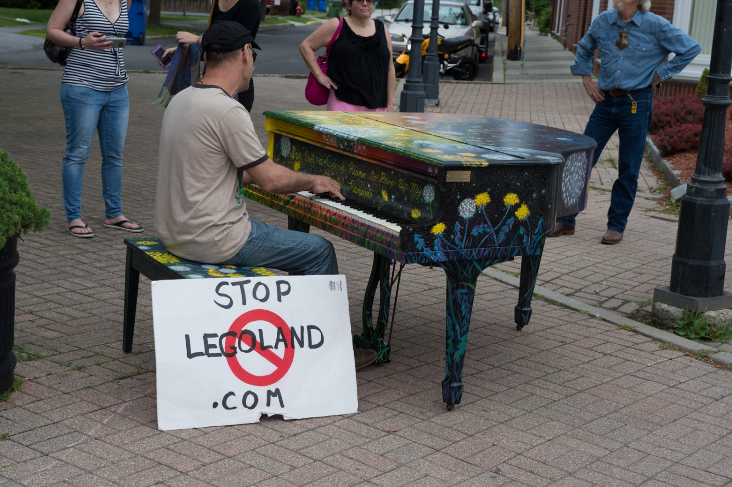 A few minutes after the launch, a local protestor puts down his sign, and has fun playing one of the pianos. Proof that art and music crosses all divides, perhaps?