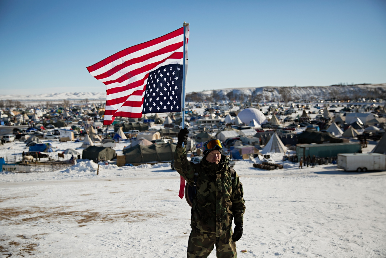 """Sargent Roger Hintson, a Marine Core veteran from San Francisco, CA, holds the US Flag in distress because while he served his country under the correct flag, """"I believe America is now in distress."""" Sgt. Hinston is part of an estimated 2000 veterans who traveled to the camp to provide protection for the Water Protectors against the law enforcement whose methods he considers excessive."""