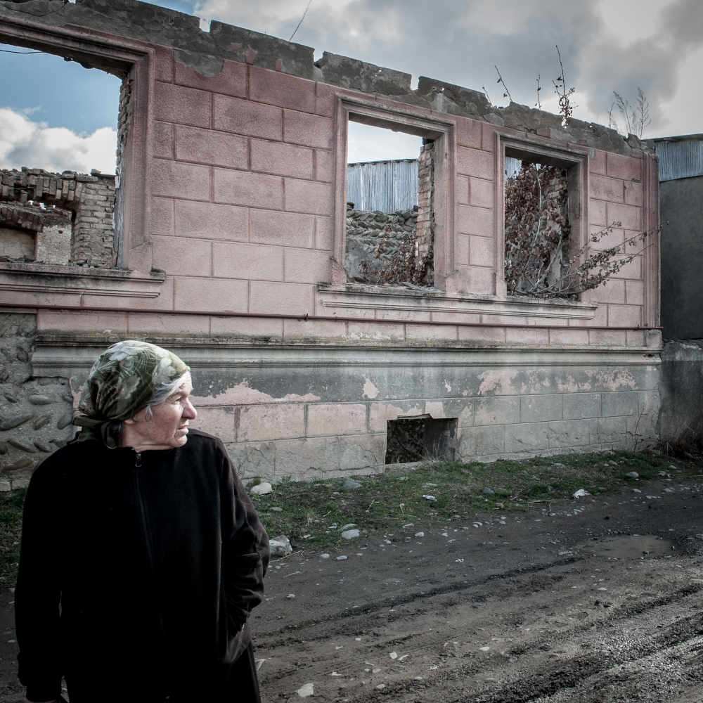 Old woman walks in front of a bomed-out house in the village of Dvani, reachable just passing through Georgian checkpoints.