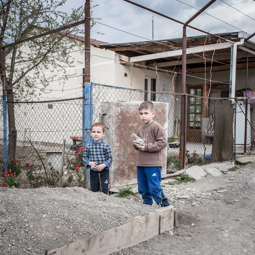 Two young boys plays in the street of the village of Kereleti, one of the refugee container camps among the ABL.