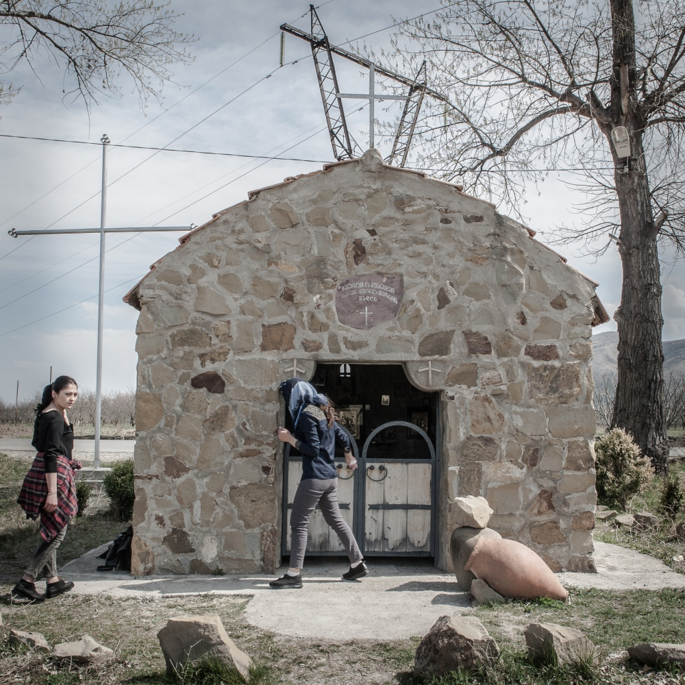 Two girls at the entrance of a chapel in the village of Sveneti, one of the cointainer refugee camp near the border with South Ossetia.