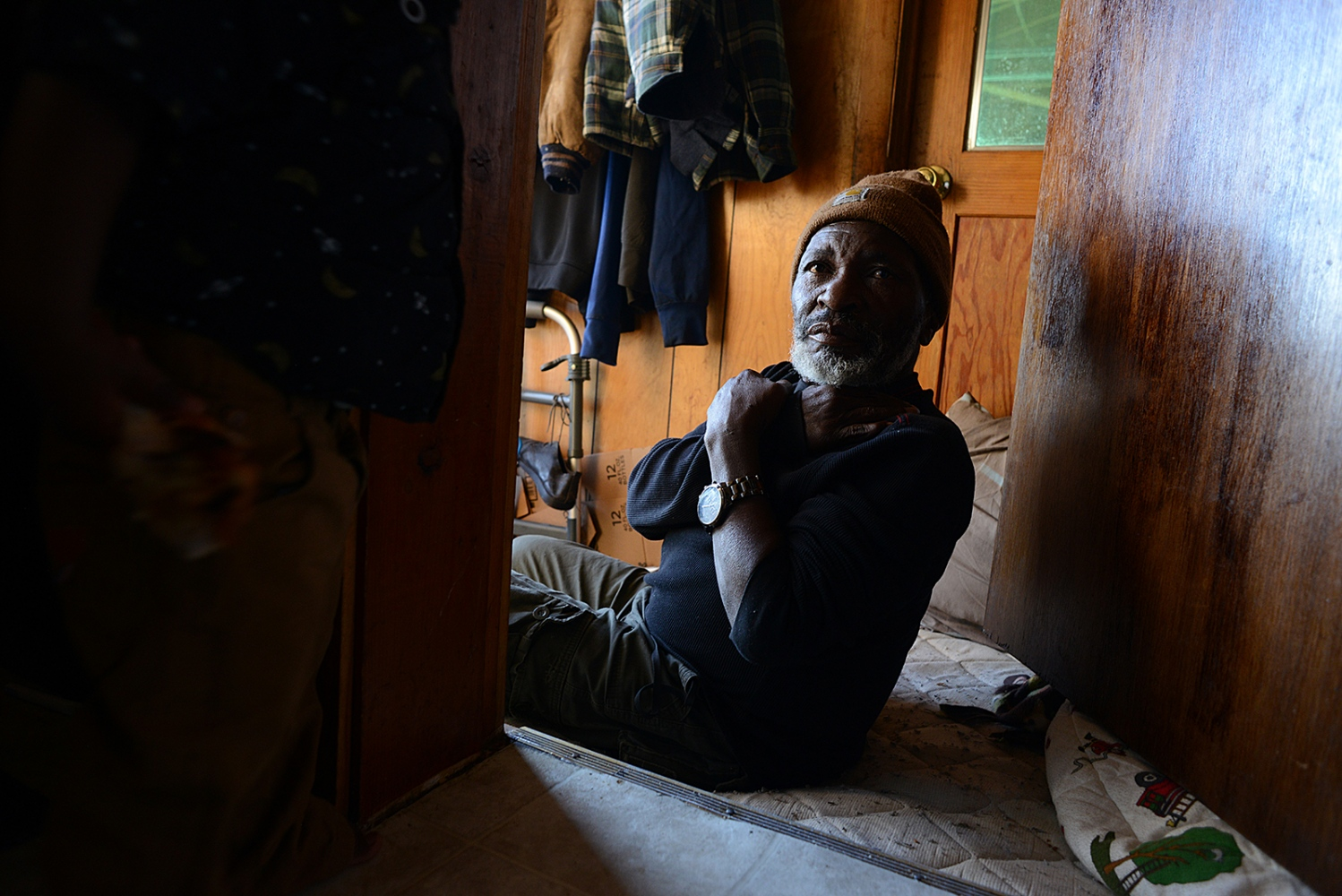 Kasereka Kanduki sits in his room, a mattress on the floor in hallway, which he shares with Pascal's family.