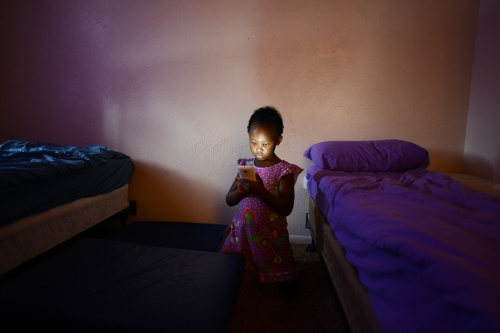 Joyce, Celestin's 5-year-old daughter, flips through photos on her father's phone.