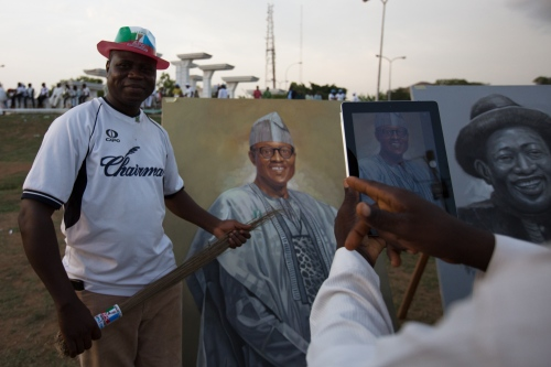 A man poses for a picture with a painting of President Muhammadu Buhari, Unity Fountain, Inauguration day, Abuja, 2015.