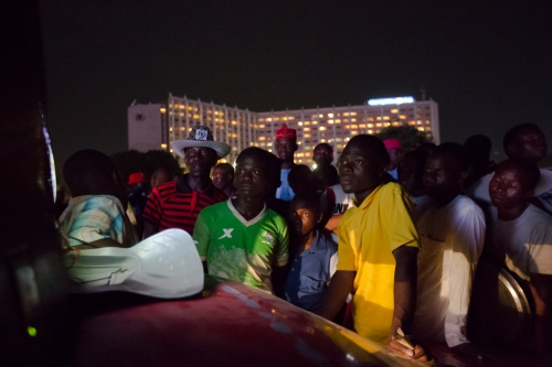Onlookers watch music videos from a TV strapped to a car. Unity Fountain, Inauguration day, Abuja, Nigeria, 2015.