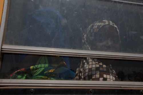 A girl who was displaced from Maiduguri, looks out the window of a bus. Yola, Nigeria, 2014