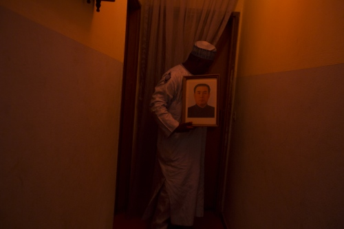 Professor Alhassan, 54, holding a picture of the former North Korean leade, Kin Jong Il, Abuja,  Nigeria, 2017. ( Buzzfeed article )