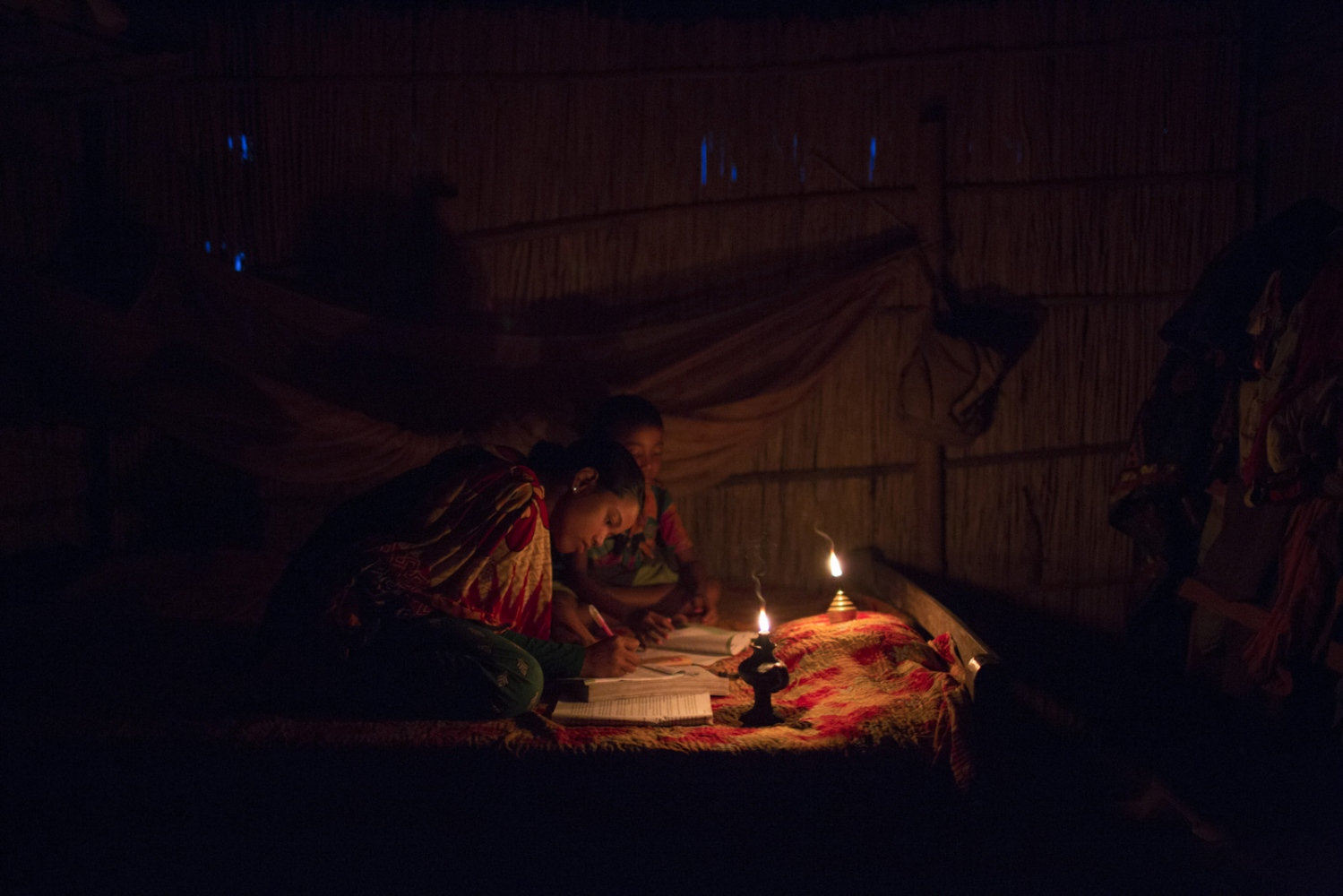 In a house Eity Rani, 14, and Shobo Rai, 8, do their homework by the light of an oil lamp. Life is much harder for children who were born in to enclaves. To go to school their parents must pay money under the table and receive a fake address. Then if they are successful the children must do their homework in the dark as no houses inside the enclaves have electricity.  Debiganj - Bangladesh