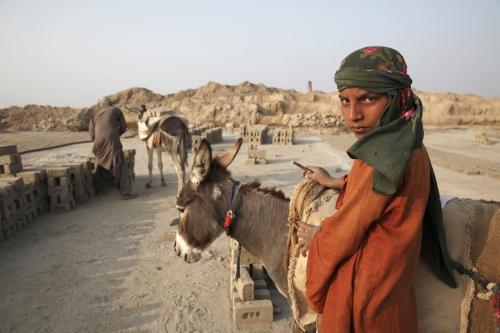 A young boy works inside a brick kiln.  Sindh Province - Pakistan