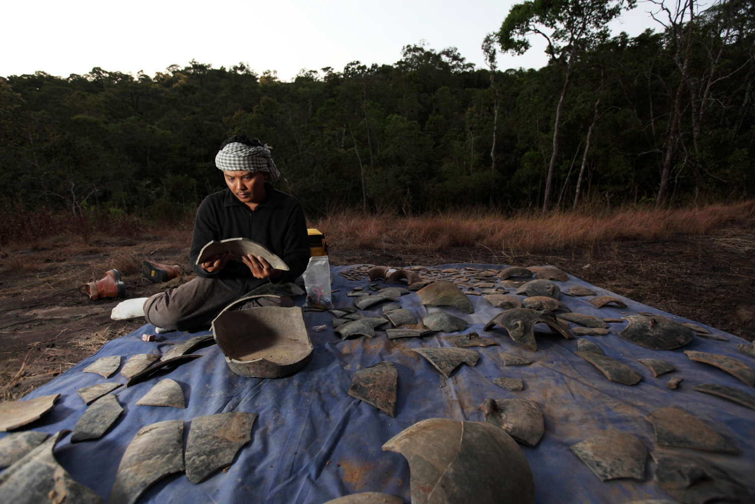 Tep Sockha, Cambodian ceramic expert, reconstructs a damaged jar probably broken by falling rocks.  Cardamom Forest - Cambodia