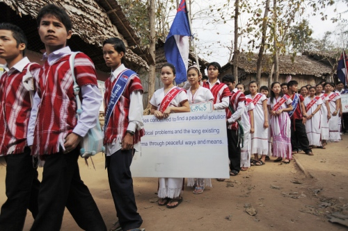 Karen refugee teenagers carry the Karen flag and boards asking for peace and an end to the Burmese war during the Revolutionary Day service in Mae La camp.  Mae La - Thailand