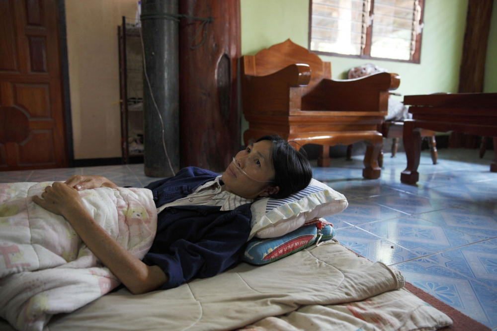 Mrs. Jiraporn Sripol, a former office cleaner at Mae Moh power plant, lies sick with cancer inside her home. It is believed the dust from the power plant led to her sickness.  Lampang - Thailand