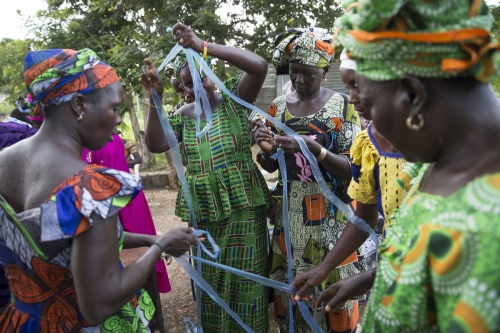 Member's of the Njau community women's group cut up a large sheet of plastic that has been donated to them by an airline that flies in and out of Gambia. The women will use this plastic to make bags and jewellery which will then be sold to visitors.  Njau Village - The Gambia