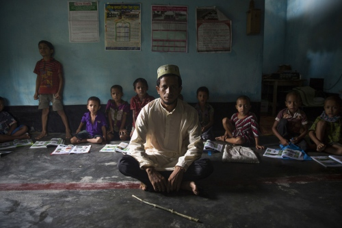 In Maja Para village in the Dhoholakhagrabari enclave young students and their teacher sit in class of a madrassa. Because enclave children have a difficult time accessing the education system in Bangladesh the locals of this enclave formed an Islamic Foundation funded on donations and built this school to give their children some form of education.  Debiganj - Bangladesh