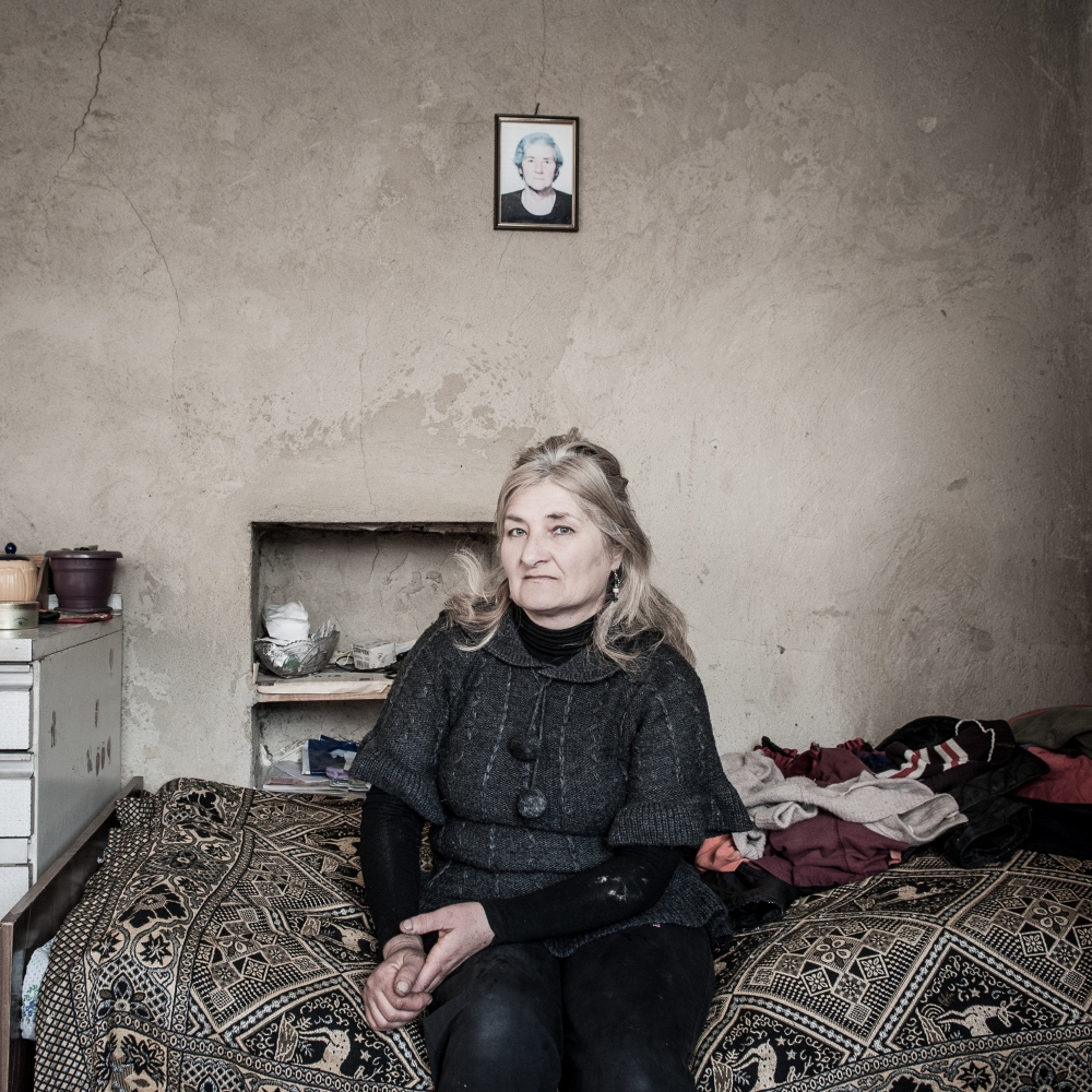 "Izo Akhalkatsi, 55, live in Dvani, her native village, still highly bombed-out. Her house is still extremely damaged and her mother (in portrait) died during the war. ""Our village is closed to the Ossetian border. They arrest people and this is our main problem. In 8 August 2008, they burnt our houses after shooting us from the hill. I, my mother and sister were trying to hide ourselves. We run away, staying behind the walls to avoid bullets. When we returned there, we saw our house destroyed."""