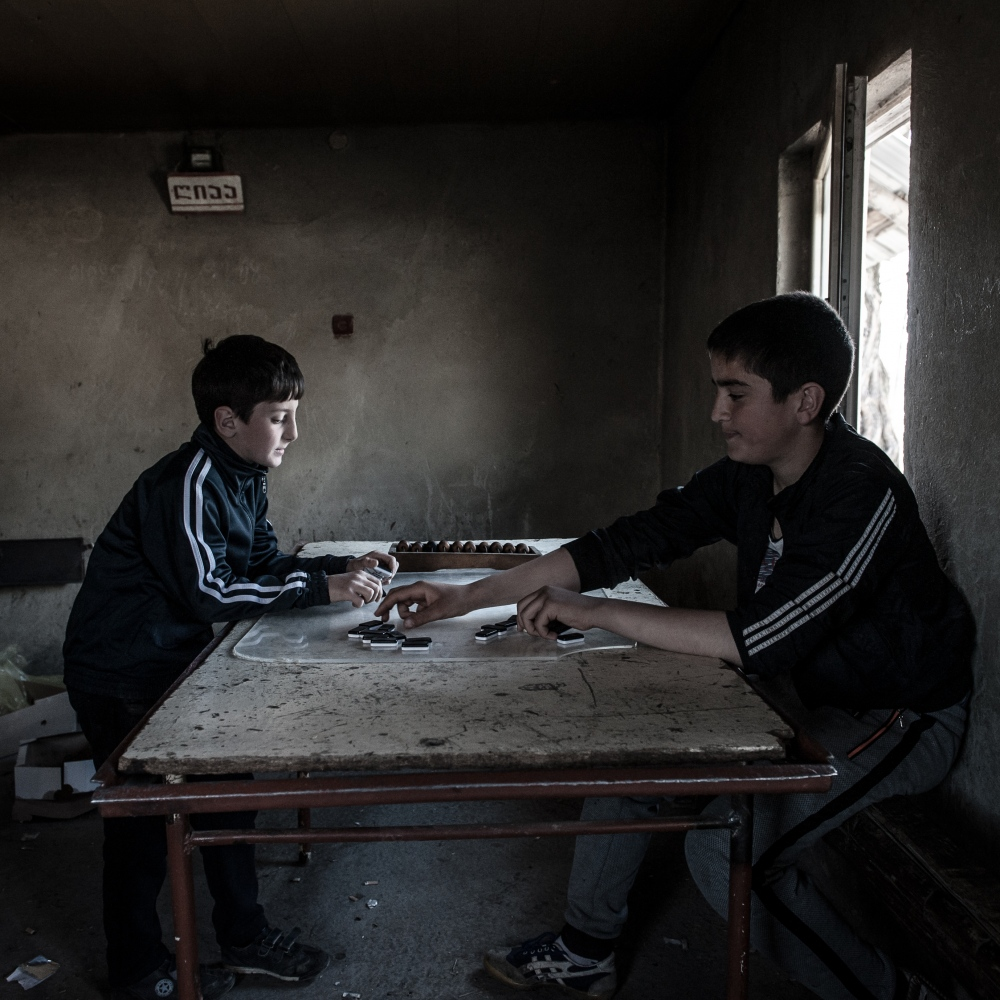 Two young boys play a traditional game in the village of Jariasheni. The building was an important shelter during the 2008 war. Here, the ABL is completely uncertain and there is no wire mesh separating Georgia and South Ossetia.