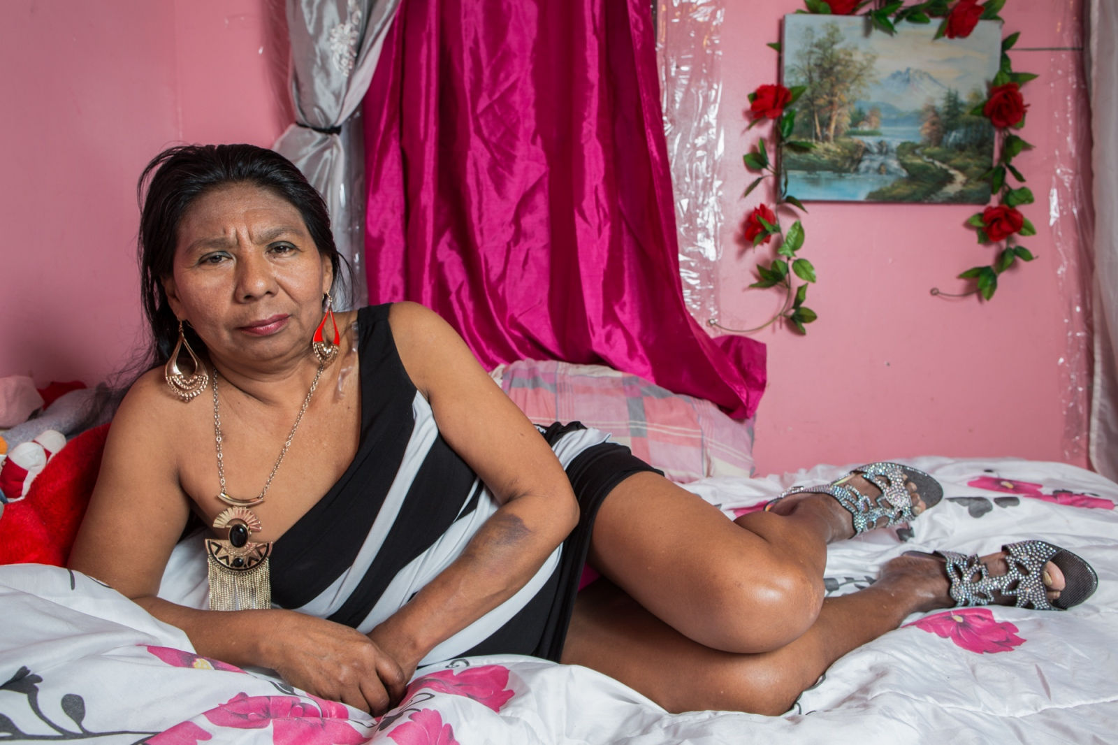"Dionisia Martínez , in her bedroom at 45th. street in Sunset Park, Brooklyn. She is a singer and dancer of Mexican folklore, born in Atencingo, Puebla, based in New York since 2002. Since then she has worked washing dishes in restaurants, selling balloons and cleaning. But her passion is singing. She is better known as ""Lupe Cantarrecio"" (Lupe ""who sings out loud""). She has a role in the documentary ""Me Voy"" (I go) directed by the film making collective Mu Media."