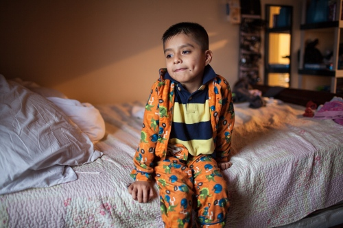 Alex Salvador sitting in one of the bunk beds in the bedroom where he sleeps next to his sisters and parents. Alex is 7 years old and understands a little of Tlapaneco, the language that his parents speak at home. Bronx, NY.