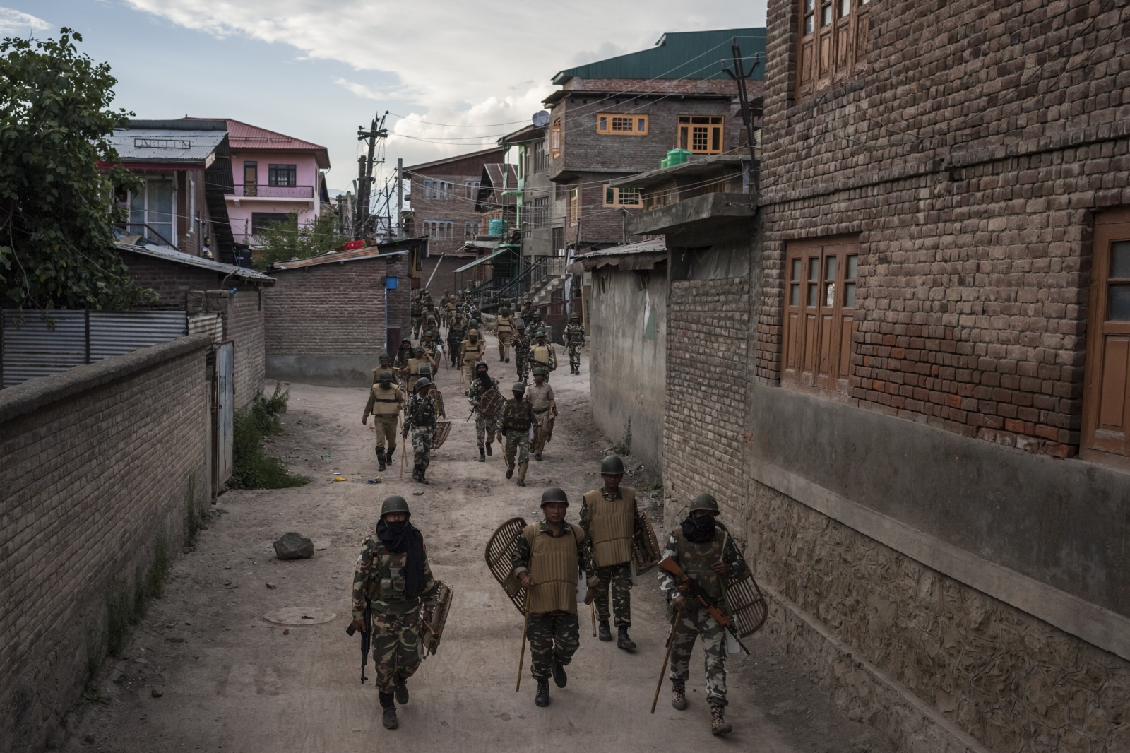 Indian Central Reserve Police Force (CRPF) and security personnel retreat following a day-long curfew and shutdown in downtown Srinagar on August 18, 2016.