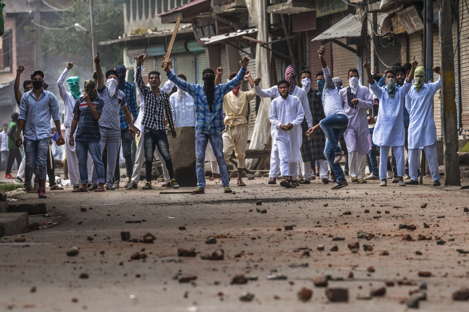 Kashmiri protesters shout slogans and throw stones during clashes with Indian Central Reserve Police Force (CRPF) and security personnel during a strict curfew on Eid-al-Adha, one of the most important religious festivals in the Muslim calendar, in the Batamloo area of Srinagar on September 13, 2016.