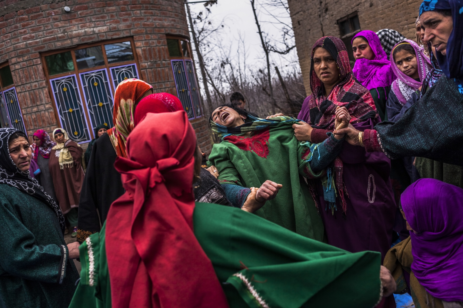 Kashmiri relative Hafeeza Khan (C), weeps during the funeral of nephew Rasiq Ahmed Khan, aged around 22, and who was found shot to death, at their home in Watchohallan village in Shopian, south Kashmir, some 80 kms from Srinagar, on December 14, 2015. Raisq, who disappeared on December 13, was found shot to death by gunmen who local residents report were members of the Indian police Special Operations Group.