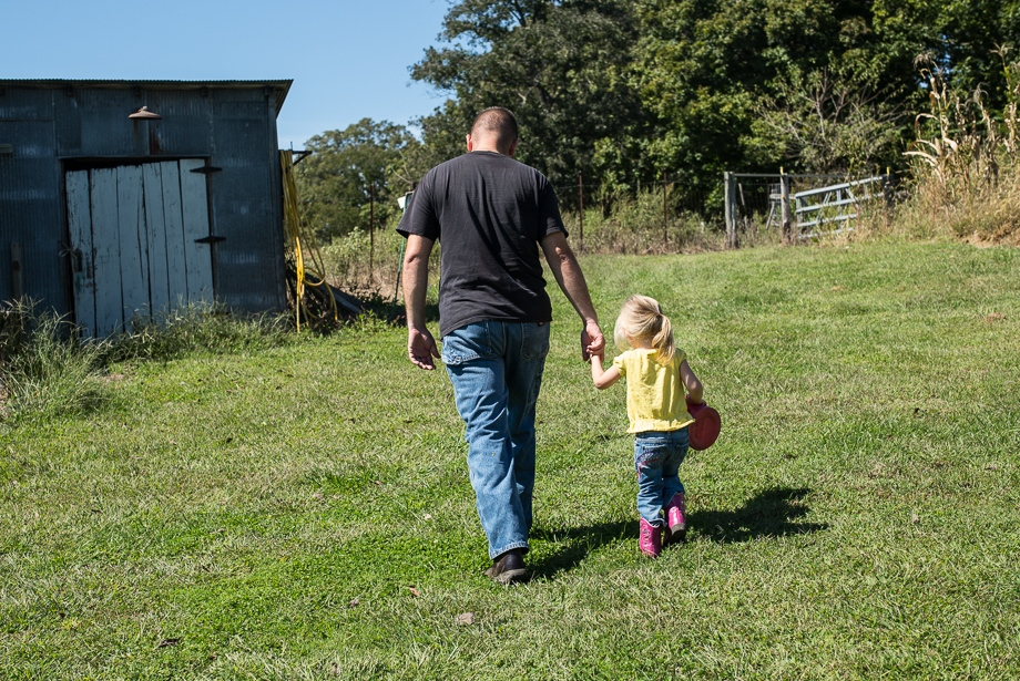 Makenzie and her dad heading to the chicken coop, which is located in the back of her grandfather's farm.