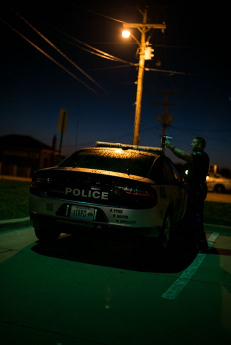 Pete grabs his morning drink off of his police car at 5:58 a.m. before he starts his shift.
