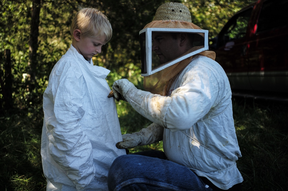 While Pete helps Jack to get into his beekeeping protective clothing, Jack waits patiently.