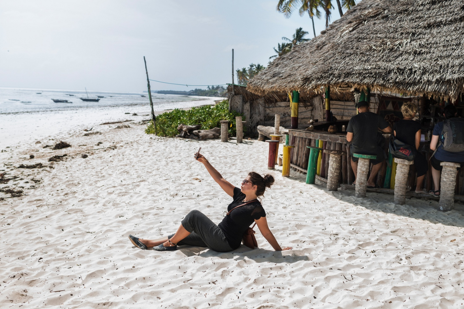 "A volunteer poses for a photo next to ""the rasta bar"" in Zanzibar."